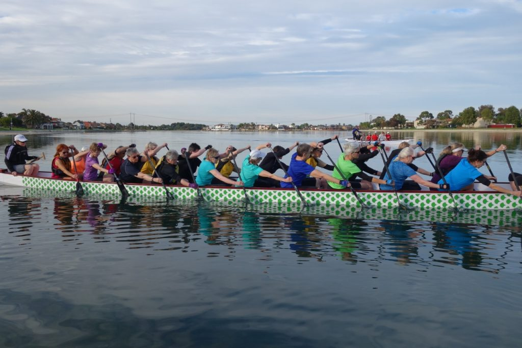 women planting paddles in synchrony