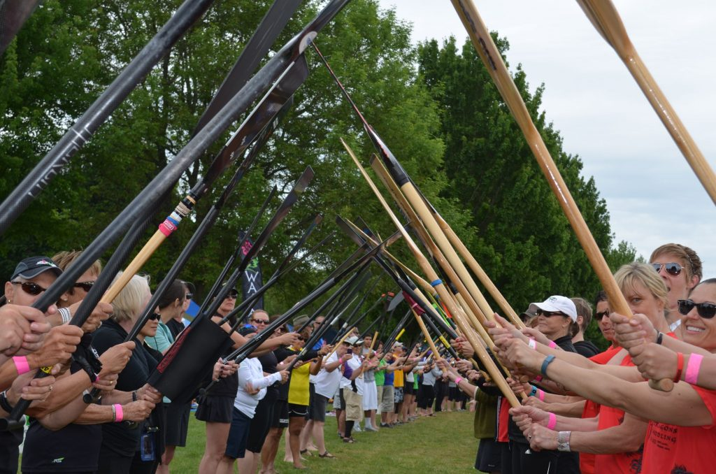 long tunnel of paddles held aloft for racers to walk down