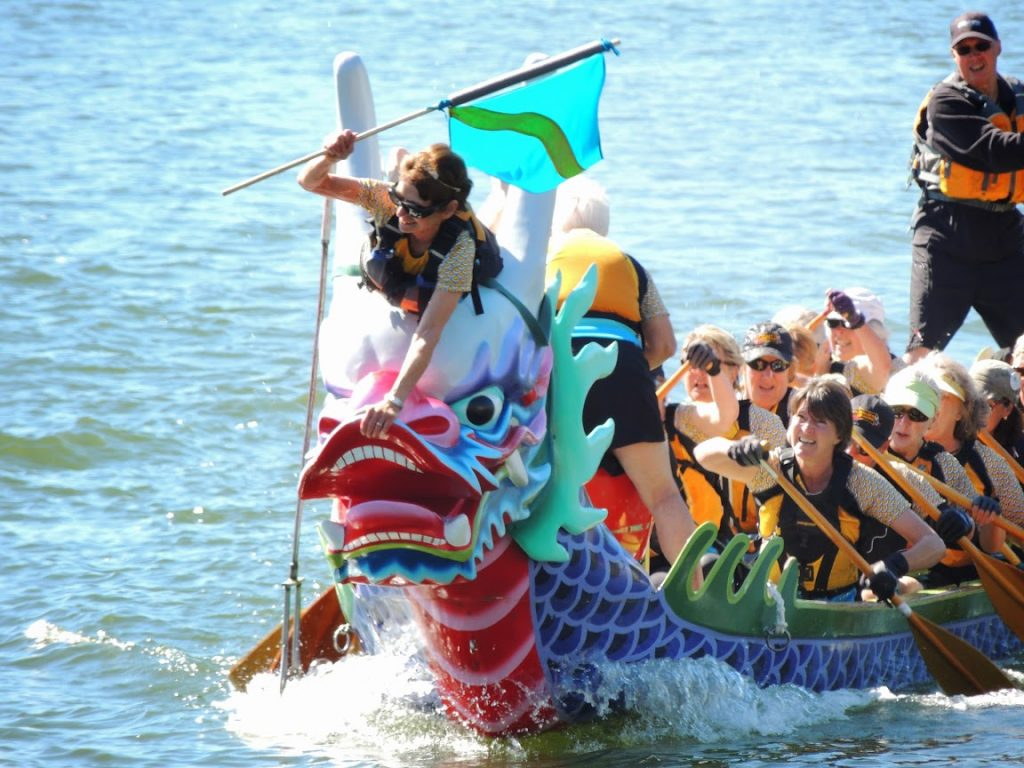 flag catcher leaning forward over nose of surging ceremonial dragon boat to catch the finish flag